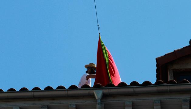 Uno de los detenidos en el momento de desplegar la bandera.