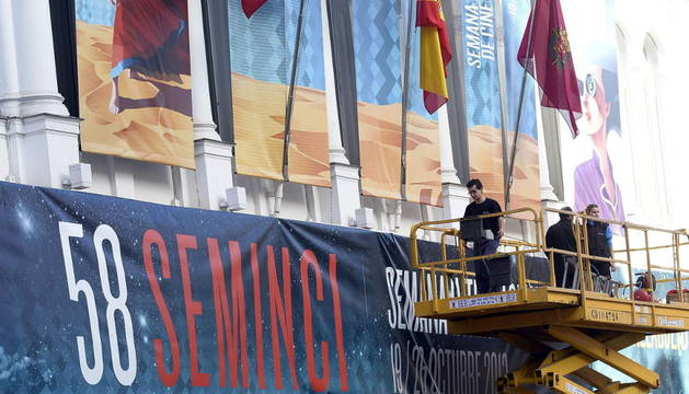 Tres operarios colocan en la fachada del Teatro Calderón de Valladolid los carteles de la Semana Internacional de Cine de Valladolid.