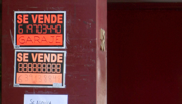 Una persona fuma junto a anuncios de venta y alquiler de inmuebles en Madrid.