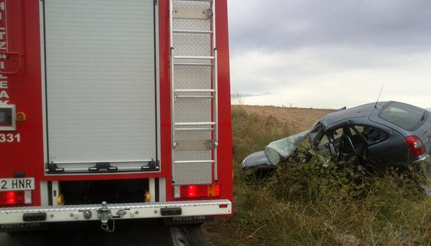 Un camión de bomberos junto al vehículo en el que viajaba la víctima.