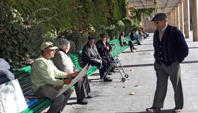 Varias personas mayores descansan en el paseo del Queiles de Tudela.