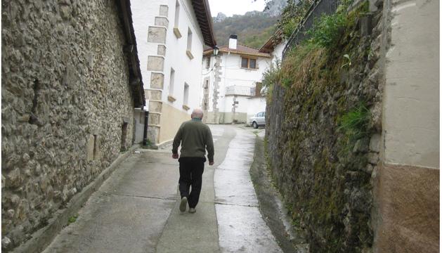 Una persona mayor transita por una calle estrecha de Lizarraga, en el valle de Ergoiena