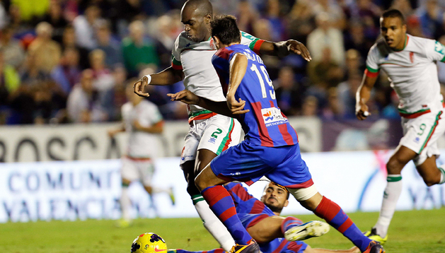 El defensa del Levante Pedro López (dcha.) disputa el balón con el defensa franco-camerunés del Granada, Allan Nyom (izda.) durante el encuentro
