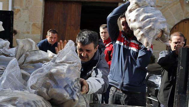 Vecinos y socios de la Peña Alegría cargan sacos de patatas en el remolque