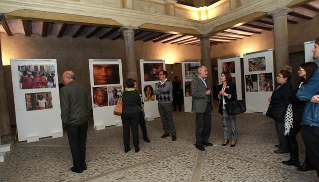 Asistentes a la apertura contemplan algunas de las fotografías de la exposición