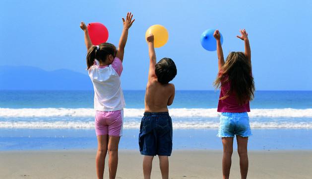 Varios niños se divierten en una playa.
