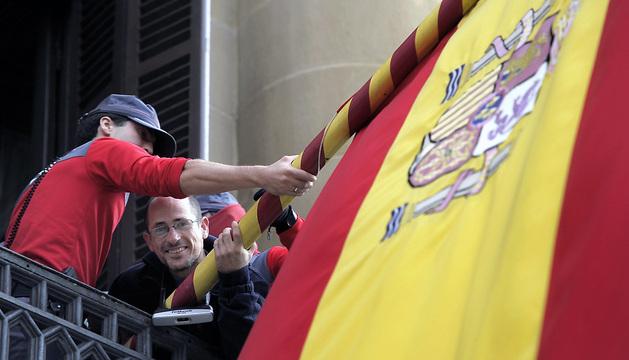 Un miembro de la plataforma Mugitu!, es desalojado del balcón del Palacio de Navarra por agentes de la Policía Foral tras encadenarse a los mástiles.