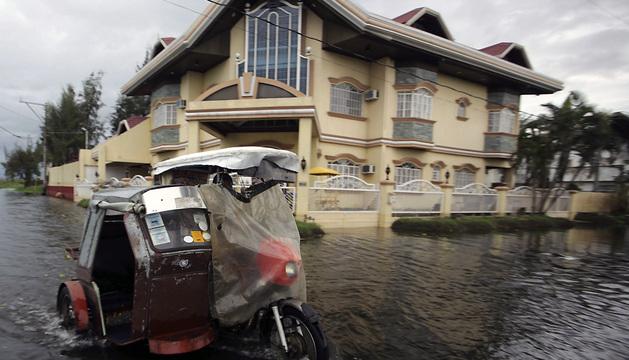 Un hombre circula con su moto por las calles inundadas de Taguig al paso del tifón