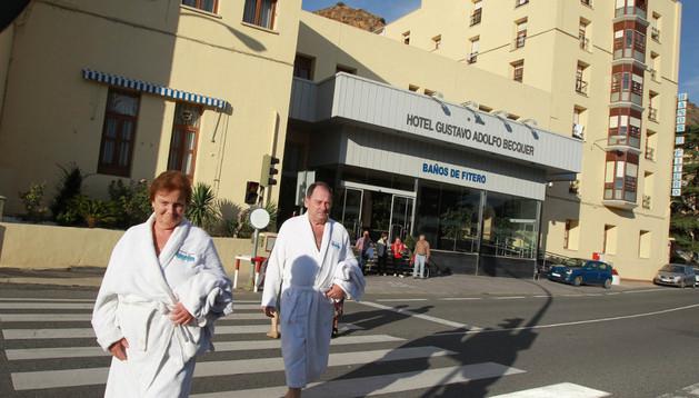 Dos usuarios del balneario de Fitero se dirigen a la piscina exterior con sus albornoces.