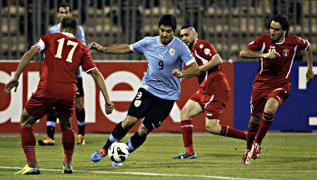 El delantero uruguayo Carlos Suárez conduce el balón rodeado de jugadores de Jordania