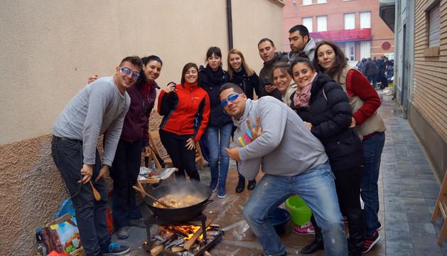 Un grupo de jóvenes prepara su comida en una calle situada junto a la plaza del ayuntamiento.