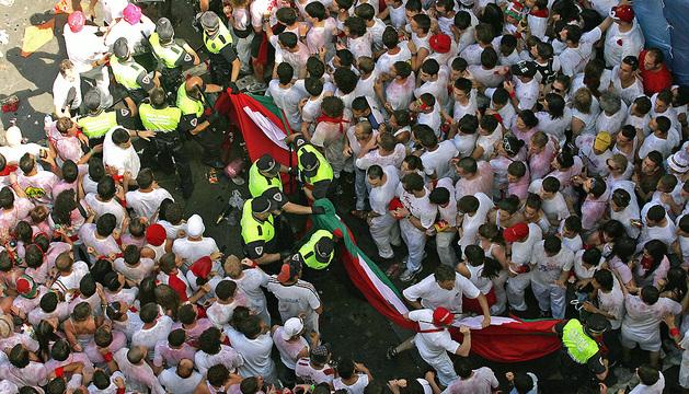 Agentes de la Policía Municipal de Pamplona retiran la ikurriña gigante durante el chupinazo de 2010.
