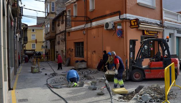 Los trabajadores municipales cambiando las losetas defectuosas en la calle San Juan de Lodosa.