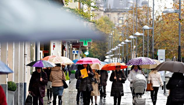 Varias personas paseando ayer por la avenida Carlos III se protegen de la lluvia
