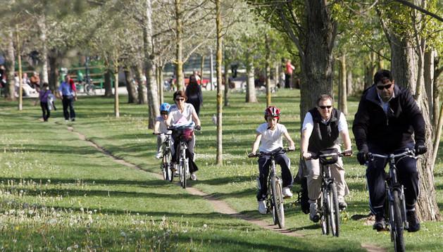 Una familia pasea en bicicleta por la orilla del Arga.
