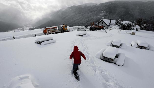 Una persona camina por un parque situado junto a la Venta Juan Pito, en el puerto de Belagoa, donde una intensa nevada caída durante este jueves dejó espesores de nieve de cerca de 60 centímetros