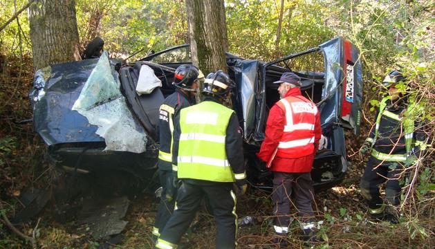 Bomberos y policías forales junto al vehículo accidentado.