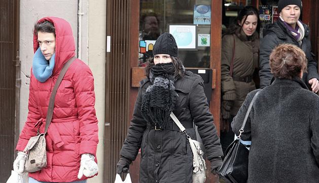 Varias personas se protegen del frío en Pamplona.