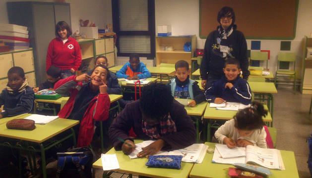 Alumnos realizan sus deberes supervisados por dos voluntarias