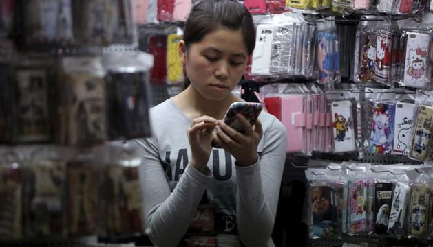 Una vendedora observa la pantalla de su teléfono móvil en China