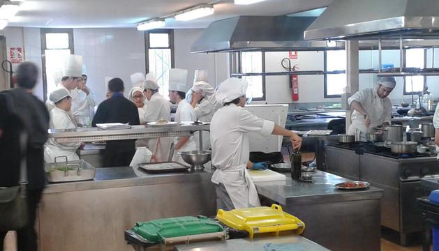 Varios estudiantes de cocina preparando la comida del viernes