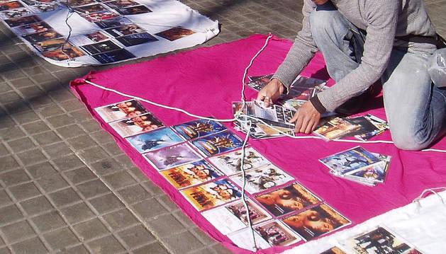 Un hombre prepara su puesto de 'top manta' con DVD pirateados.