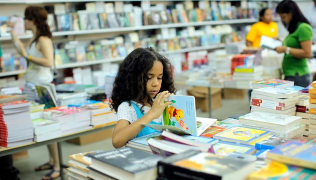 Una niña ojea un libro en una librería en Santo Domingo