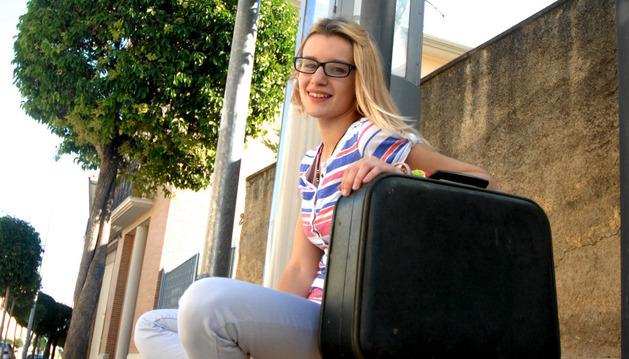 La falcesina Adela Pejenaute San José, con una maleta en la parada de autobús del pueblo