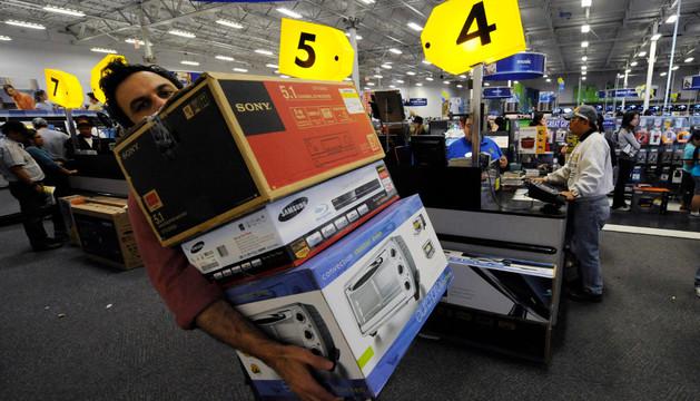 Un hombre carga con sus compras en un 'Black Friday'