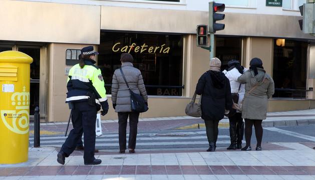 Una agente de la Policía Municipal vigila a varios peatones que van a cruzar un paso de cebra