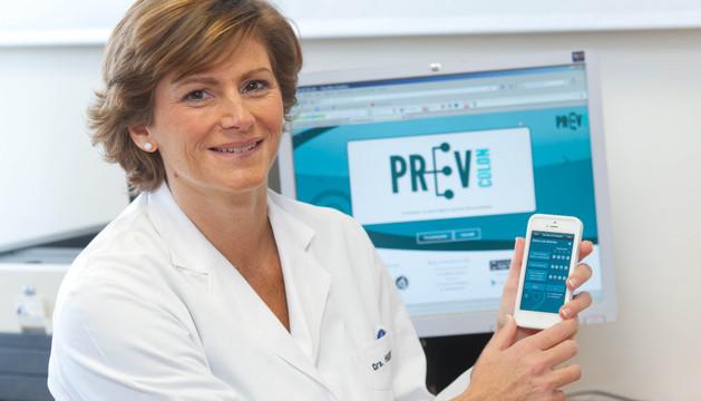 La doctora Maite Herraiz sostiene un teléfono con el que se puede consultar la aplicación PrevColon