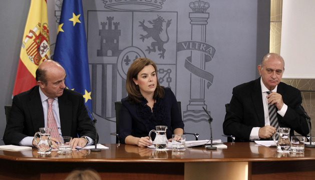 La vicepresidenta del Gobierno, Soraya Sáenz de Santamaría, el ministro de Economía, Luis de Guindos (i), y el del Interior, Jorge Fernández Díaz (d), durante el anuncio de la nueva ley este viernes.