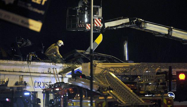Miembros de los equipos de rescate trabajan en el tejado del pub de Glasgow.