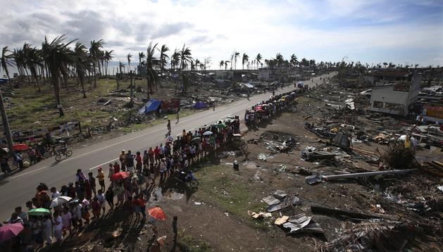 Una multitud de afectados por el Tifón Haiyan hace cola para recibir ayuda humanitaria en la devastada ciudad de Tacloban.