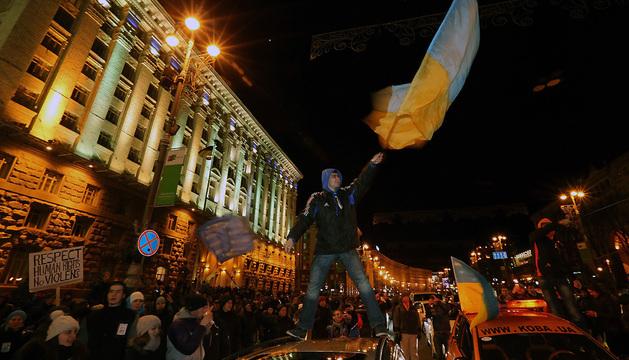 Manifestantes ondean banderas nacionales de Ucrania durante una manifestación masiva en la plaza de la Independencia en Kiev.