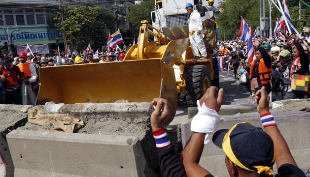 Manifestantes antigubernamentales utilizan una excavadora para atravesar las barricadas colocadas por la Policía.