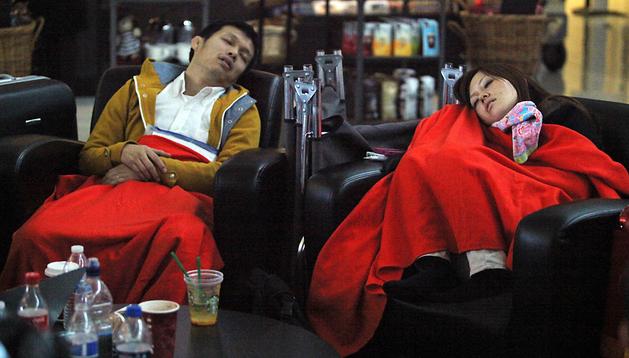 Dos de los pasajeros afectados tratan de dormir en la terminal de Dallas