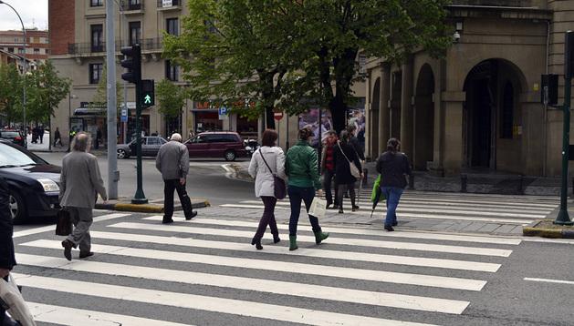 Varias personas cruzan un paso de peatones en Pamplona.
