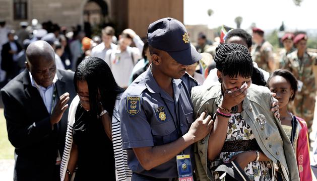 Dos mujeres son consoladas en el velatorio de Mandela