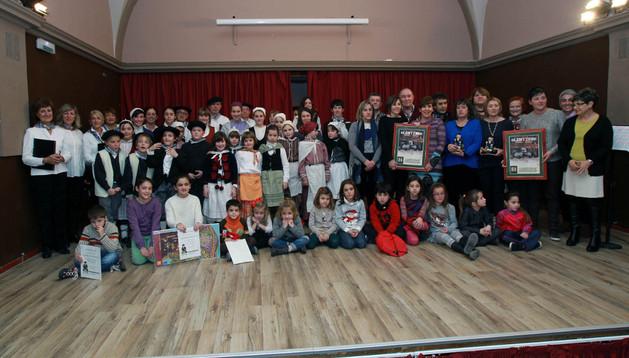 Miembros de las dos plataformas premiadas, a la derecha, junto a los niños ganadores del dibujo del Olentzero (sentados) y los miembros del coro Tutera Kantuz de ikastola Argia