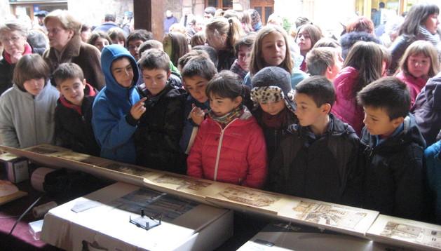 Un grupo de menores contempla unos grabados en un puesto de artesanos en la feria del viernes