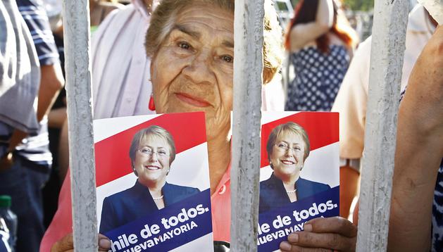 Una seguidora de Michelle Bachelet sostiene un cartel de la candidata ganadora en Chile