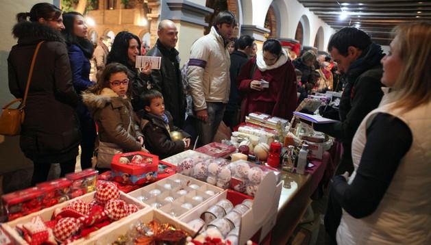 Un grupo de personas contempla los adornos de Navidad de uno de los puestos de la feria
