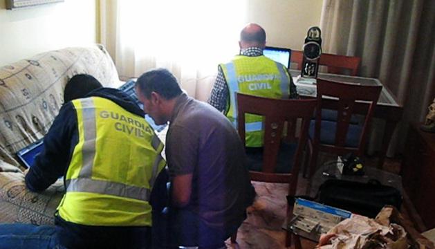 Agentes de la Guardia Civil analizan el material informático incautado.