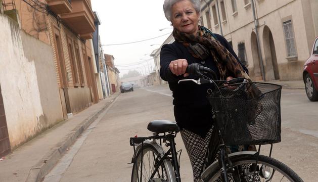 Herminia Huguet Peralta posa junto a su inseparable bicicleta en una de las calles de su Ribaforada natal.