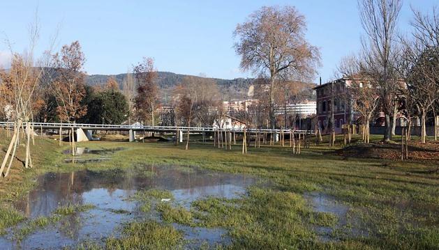 El bosque de crecida a la altura de Casa Irujo (derecha), con una laguna de maduración para acumular el agua y la pasarela peatonal