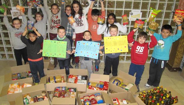 Alumnos de Santa Ana posan junto a alimentos donados estos días antes de que Cáritas pasara a recogerlos.