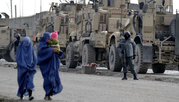 Unas mujeres pasan por delante de un convoy militar