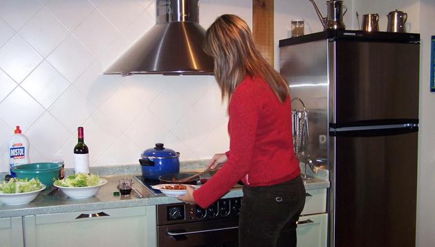 La luz es un bien esencial en los hogares. Una mujer prepara la comida en una placa vitrocerámica