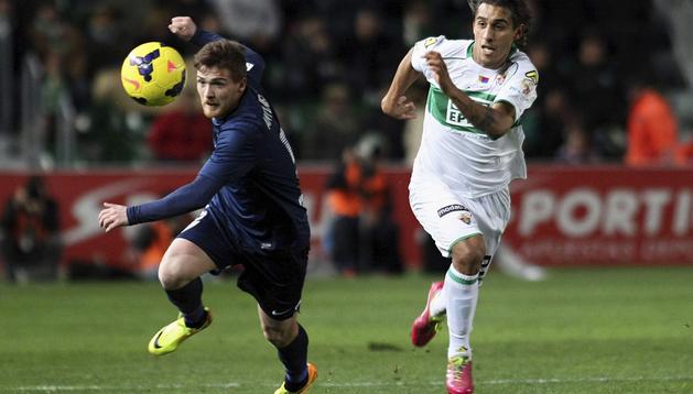El lateral uruguayo del Elche Damián Suárez (dcha.), que acabó expulsado, persigue un balón junto al chileno Pedro Morales